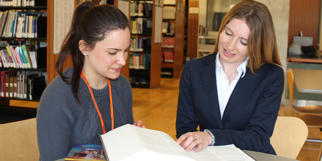 2 women looking at a reference book in the library