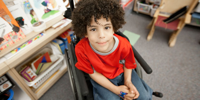 Little boy in wheelchair in the library.