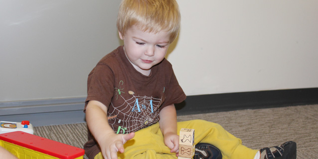 Young boy playing with blocks.