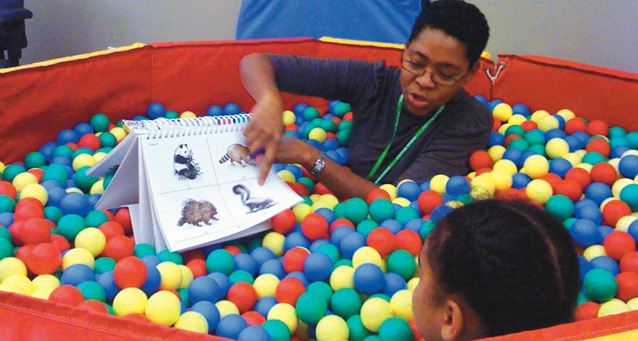 An adult and child in the ball pit reading a book in the playroom.