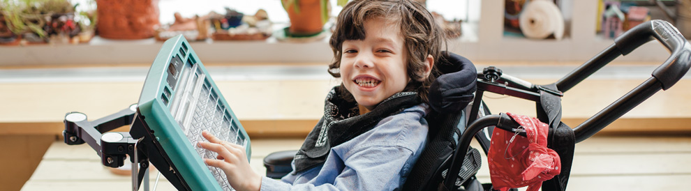 Boy in wheelchair with a special keyboard.