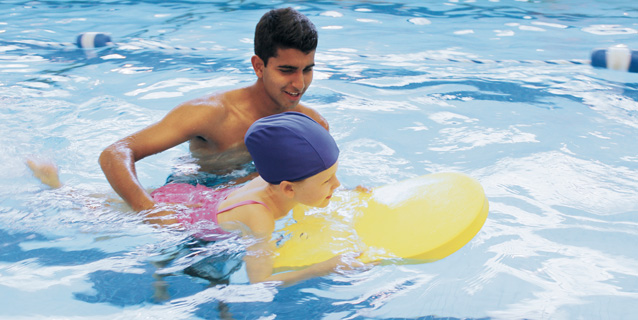 Volunteer assisting a child in the swimming pool