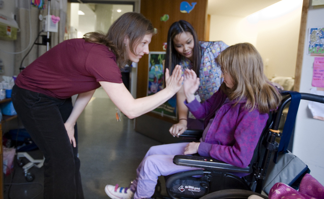 Staff high-fiving a girl in a wheelchair.