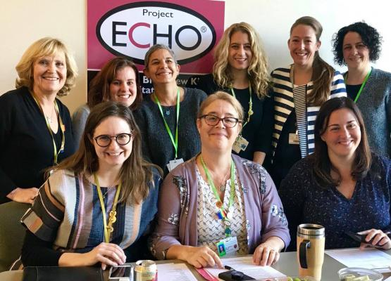 A group of woman in front of a sign that says Project ECHO
