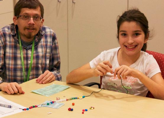 Child life specialist helps girl make bravery bead necklace