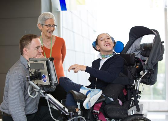 Teen girl in wheelchair with a communication system beside two adults