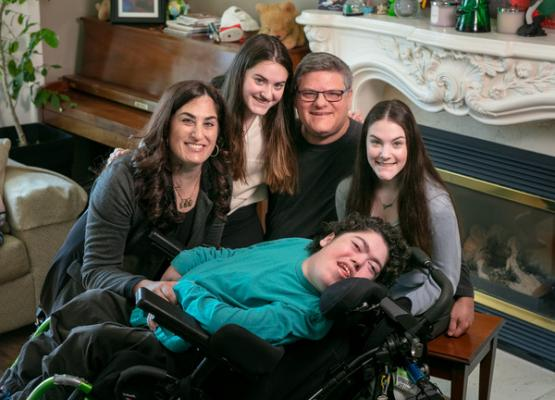 Young man in a wheelchair surrounded by sisters and parents