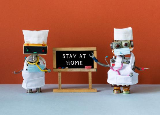 Two robots dressed as doctors with Stay at Home sign