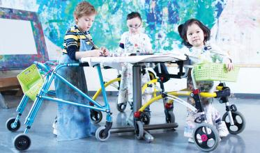 Three children using mobility devices painting around a table.
