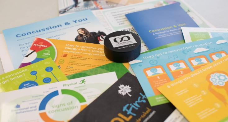 Close up of printed concussion education resources spread out on a table.