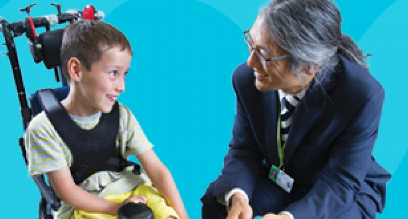 Dr. Chau conversing with a child with a disability