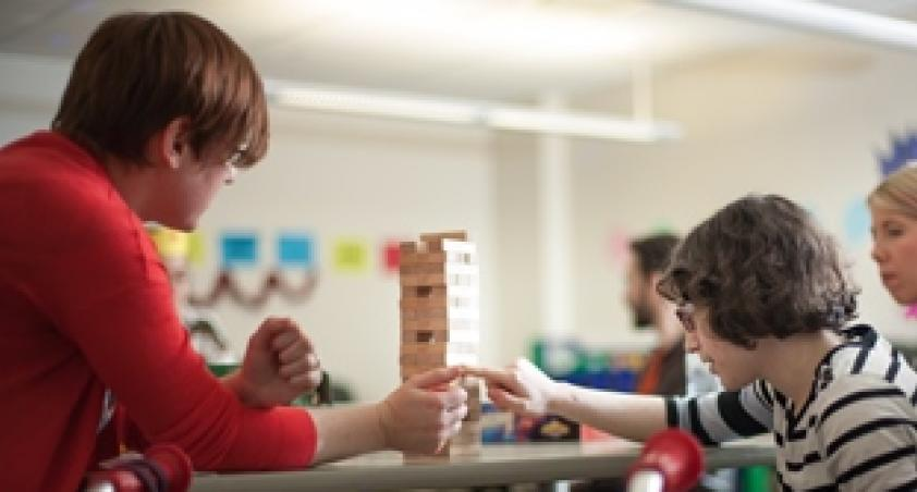 Woman and boy building a tower of wooden blocks