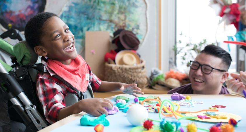 A little boy in a wheel chair playing with arts and crafts at a table