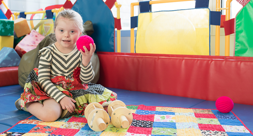 Little girl holding a red ball sitting on a quilt in a playroom