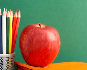 apple and colouring pencils on a desk