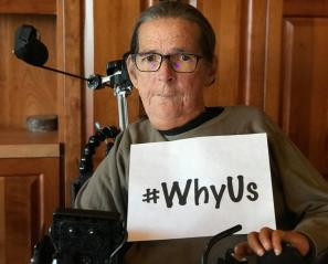 Woman in wheelchair holding sign that says #WhyUs