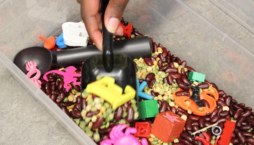 A bucket of beans and knick knacks that Rashan Edwards uses as a sandbox search activity.