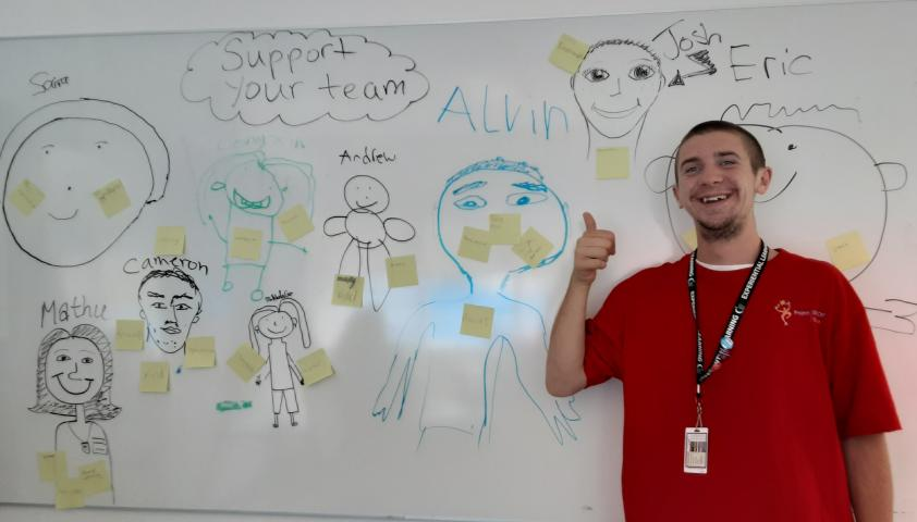 Student standing in front of a whiteboard that says Support Your Team.