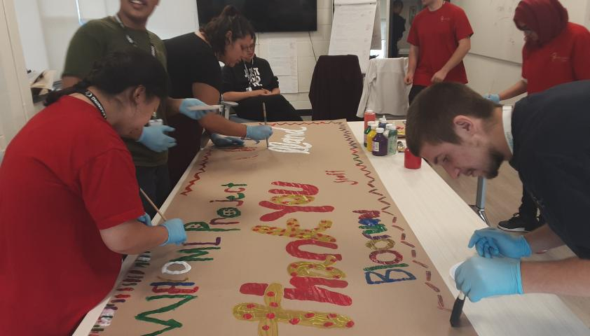 Students painting a thank you banner.