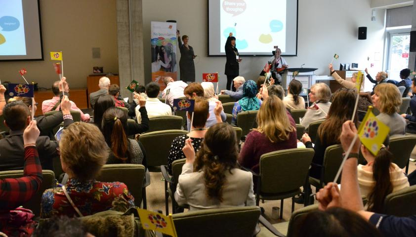 The audience waves flags in a show of support to engage in more positive conversations between health care providers and kids with disabilities after the first research panel's presentation.