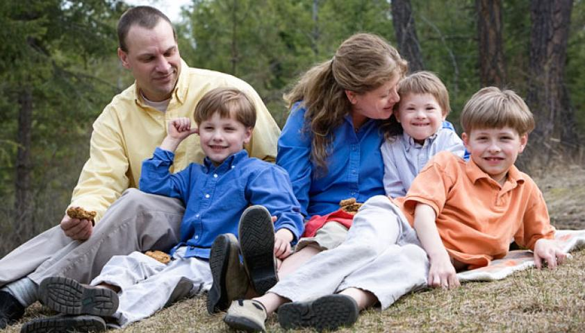 Avery and his family sitting on the grass