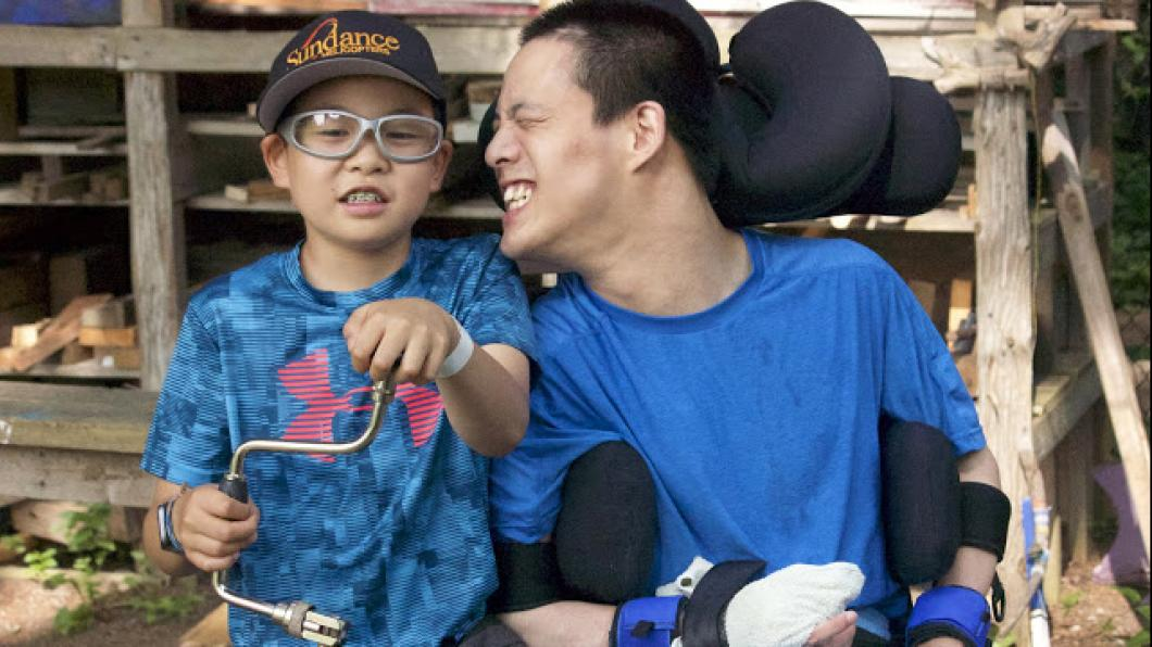 Youth in wheelchair poses with younger boy