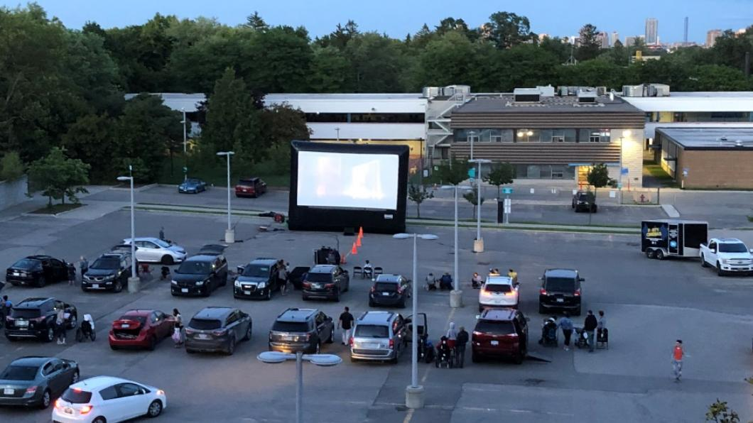 A wide view of the drive-in movie theatre in the parking lot.