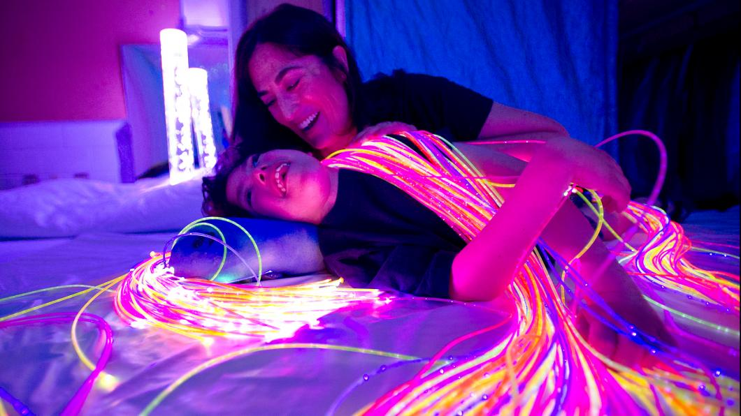 Mother and teen in dim light with fibre-optic lights draped on them