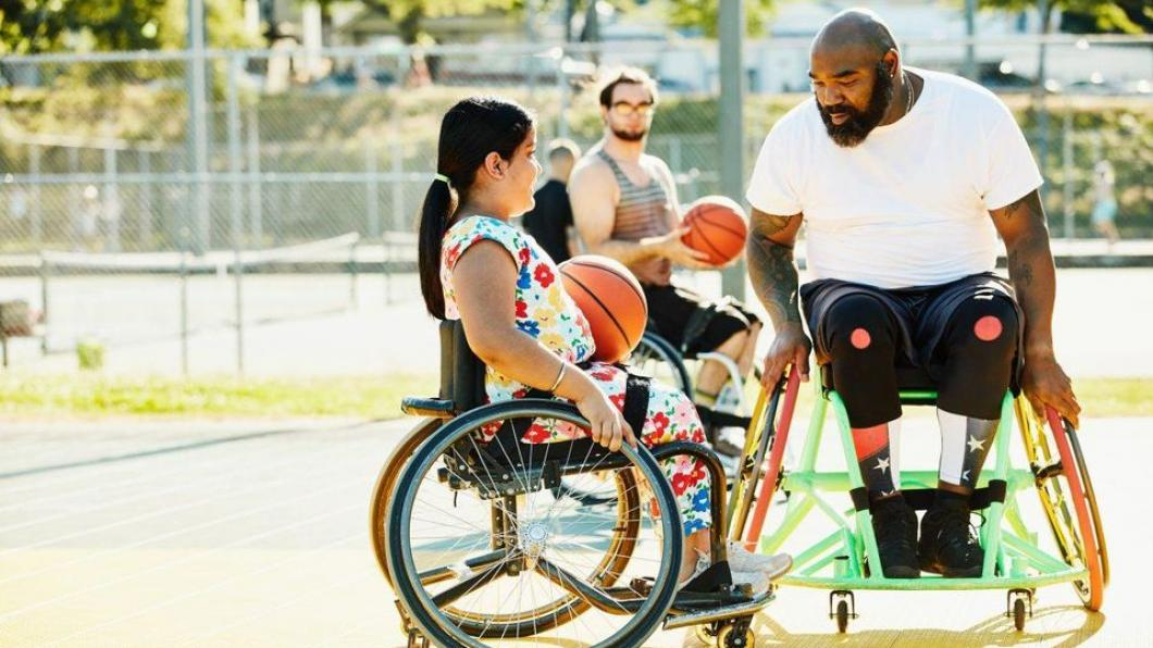 Man and girl in wheelchairs playing basketball