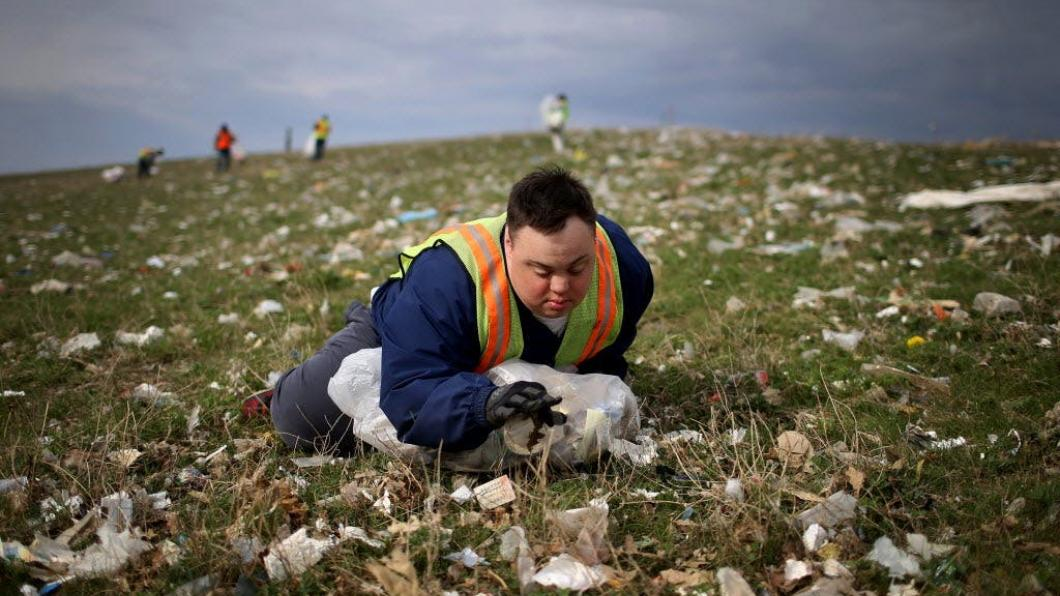 Young man with Down syndrome lying in field of garbage picking up trash