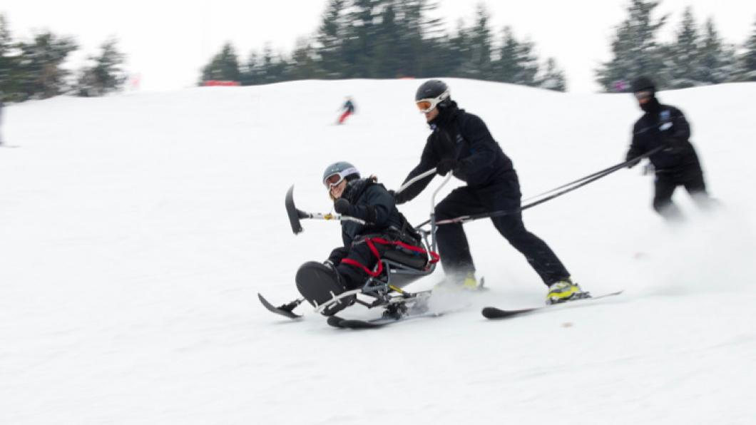 Woman descends hill on sit ski tethered to two volunteers