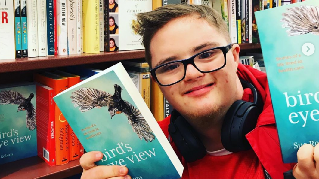 Young man holding book in book store