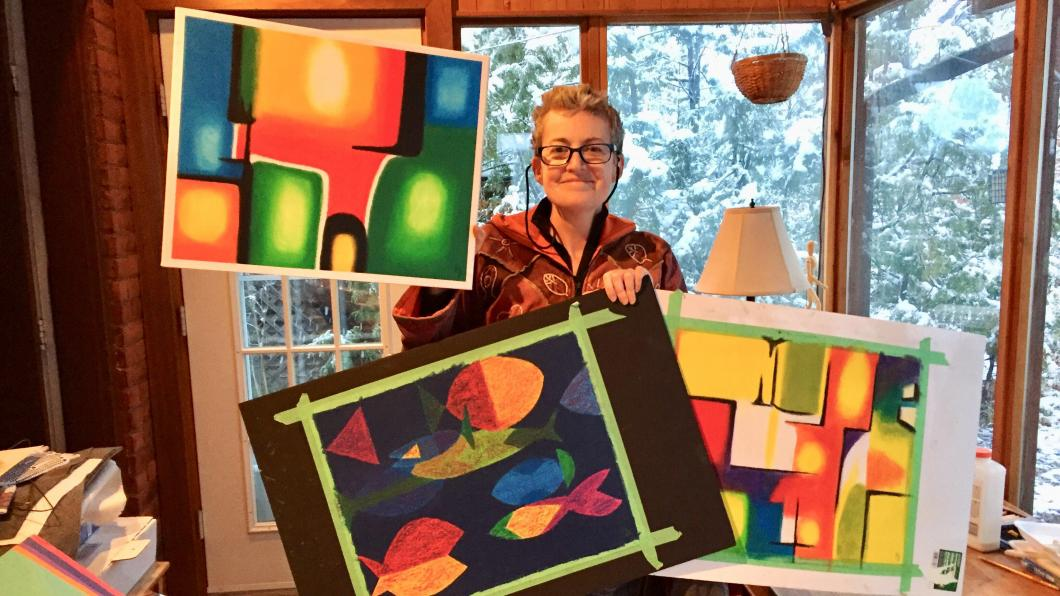Woman holding bright abstract paintings