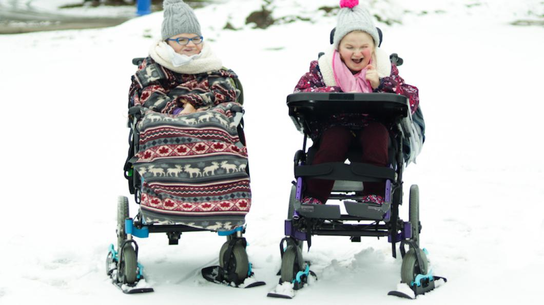 Girls in wheelchairs with mini skis under the wheels