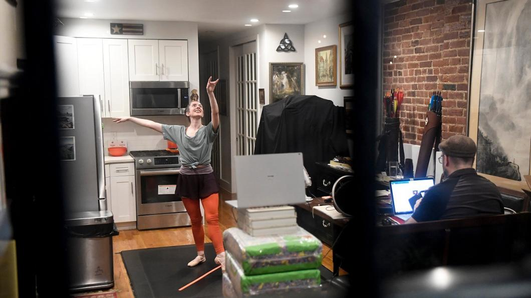 Woman doing ballet in kitchen in front of laptop
