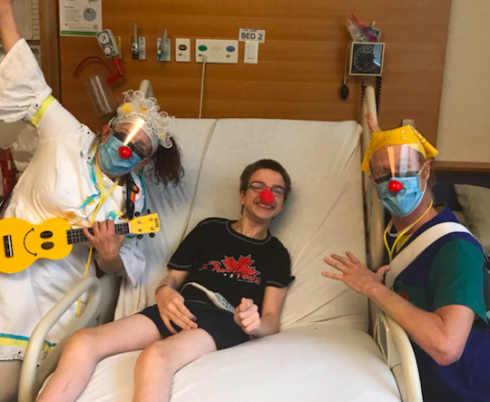 Andrew in bed with a red nose, with the therapeutic clowns posing by his bedside.